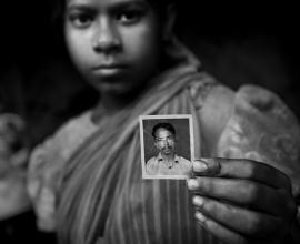 """""""Anwara"""" with a photograph of her stepfather"""