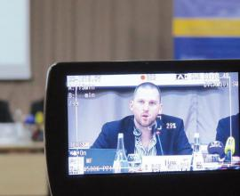 A camera filming a man speaking at a panel